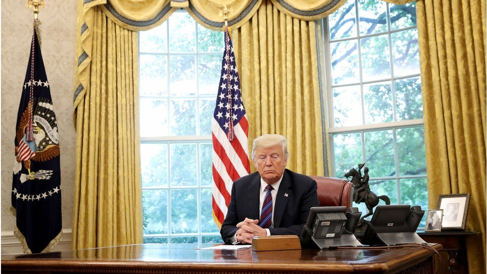 President Donald Trump speaks on the telephone via speakerphone with Mexican President Enrique Pena Nieto in the Oval Office of the White House on August 27, 2018