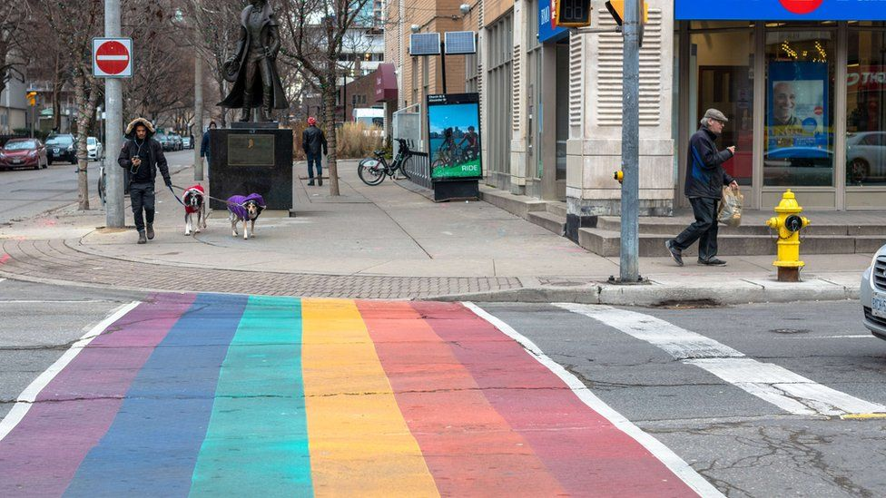 A city crosswalk painted in the rainbow colours of the LGBT flag in downtown Toronto