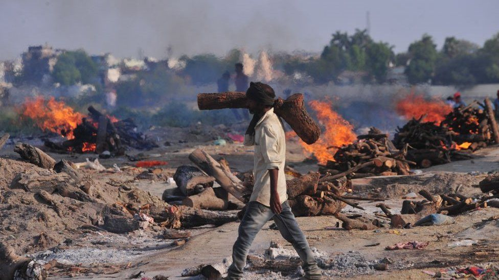 A crematorium worker carries wood for the cremation of victims who died from Covid-19 in Allahabad, India
