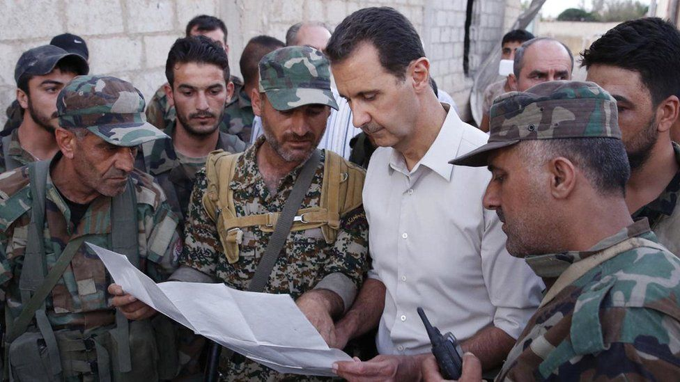 Syrian President Bashar Assad, second right, speaks with Syrian troops on the frontline outside Damascus (26 June 2016)