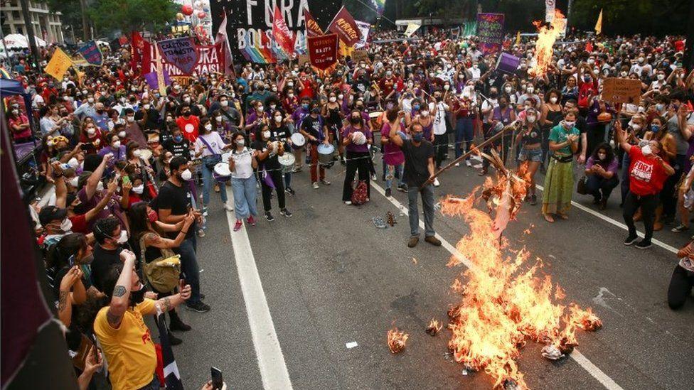 Demonstrant pali lalkę reprezentującą prezydenta