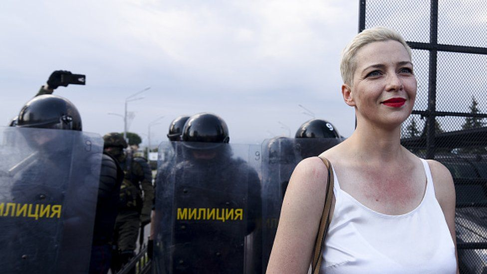 Maria Kolesnikova at a protest, with riot police seen behind her