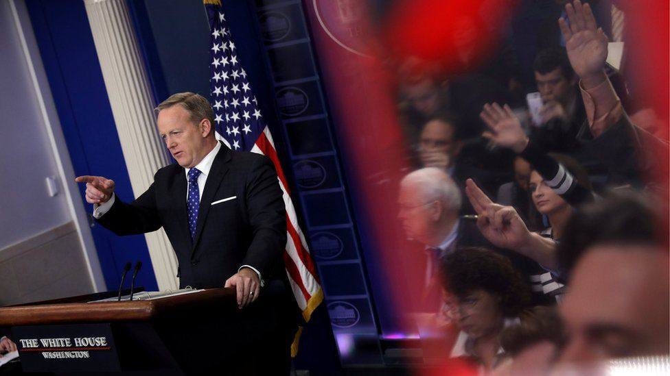 Journalists are reflected as White House spokesman Sean Spicer holds a press briefing at the White House in Washington