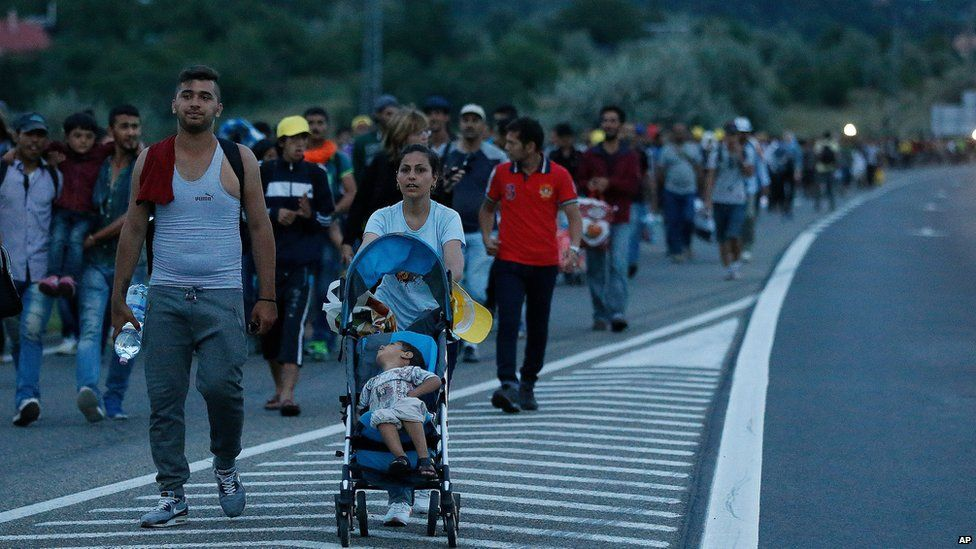 Migrants walk in a long line along the highway near Budapest, Hungary, Friday, Sept. 4, 2015.