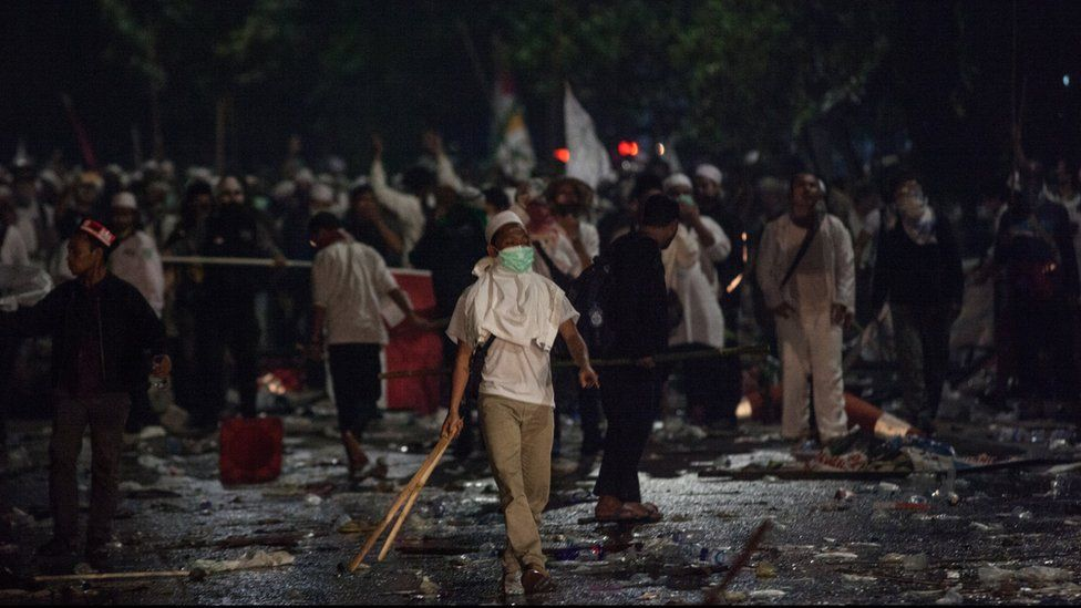 Protesters carrying sticks and wearing masks challenge police at a rally that turned violent on 4 November 2016 in Jakarta, Indonesia.