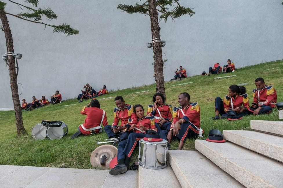 Members of a marching band sit on grass.