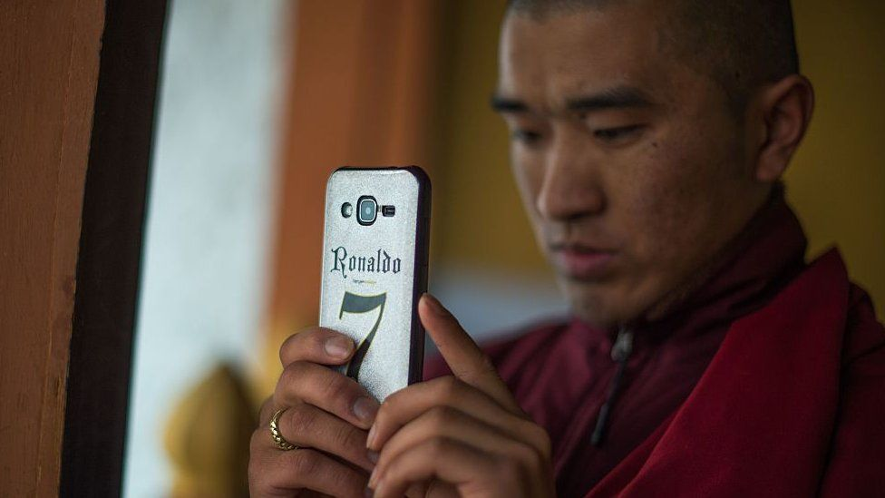 A Bhutanese Buddhist monk uses his mobile phone to take a photograph