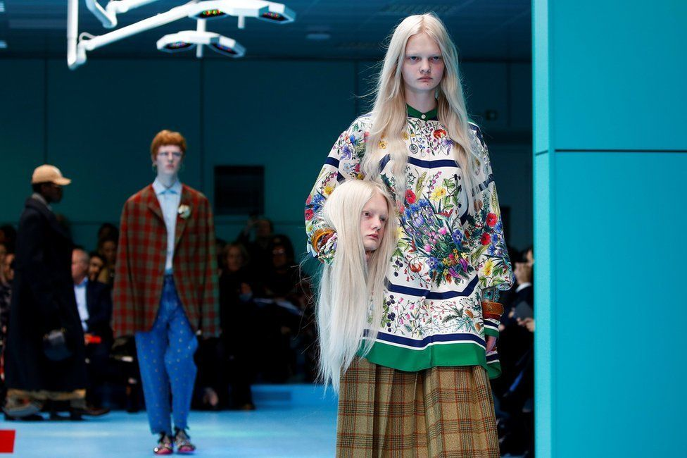 Female model in floral dress walks down the catwalk holding a mannequin head that is a replica of her head