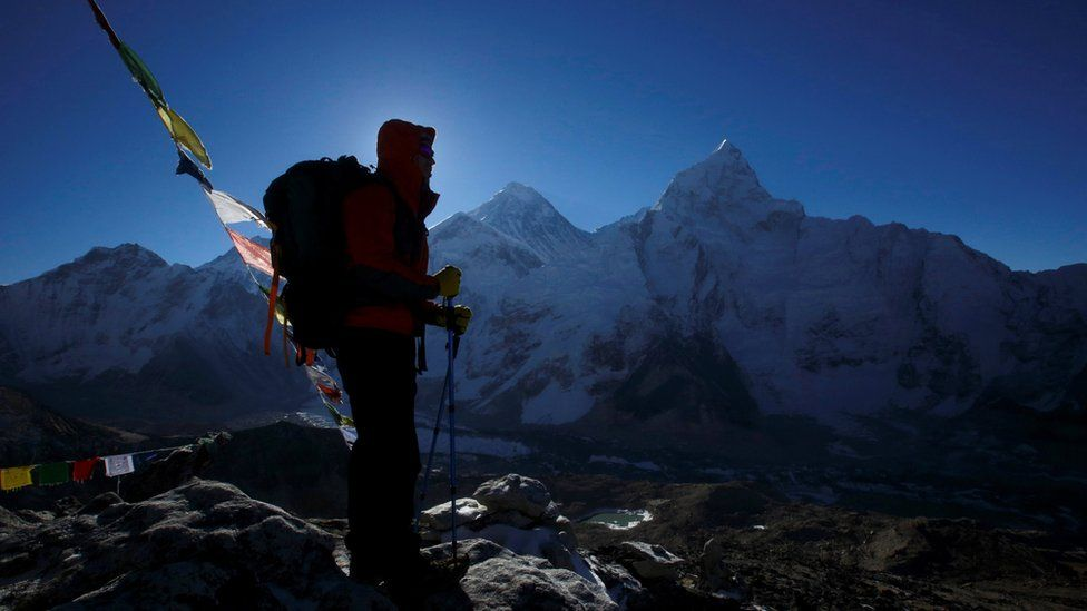 A trekker stands in front of Mount Everest, which is 8,850 meters high (C), at Kala Patthar in Solukhumbu District May 7, 2014