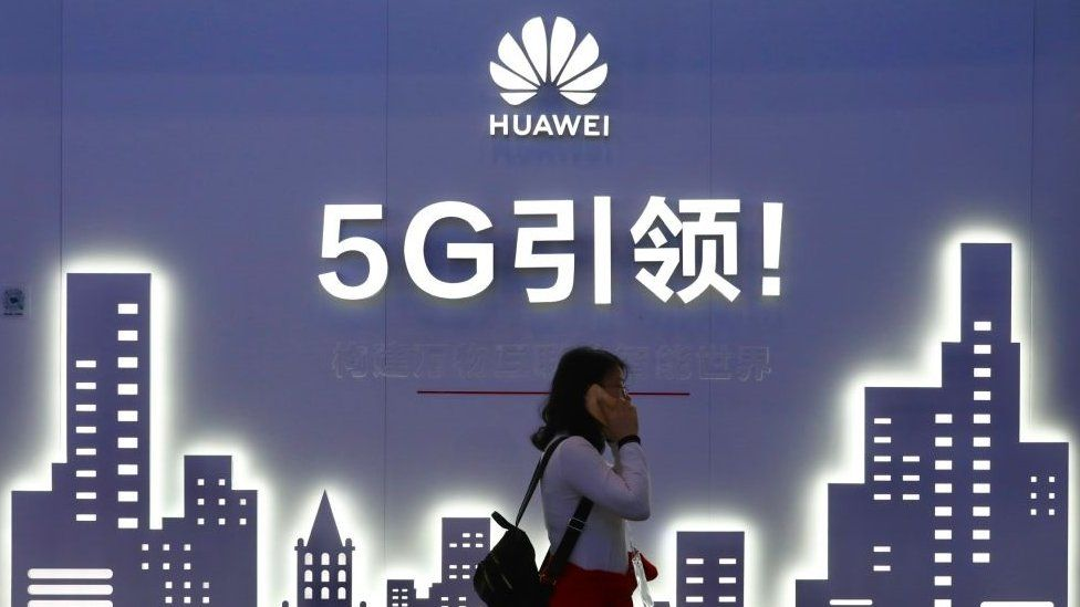 A woman walks past Huawei 5G sign on the opening day of PT Expo China 2019 at the China National Convention Center on October 31, 2019 in Beijing, China.