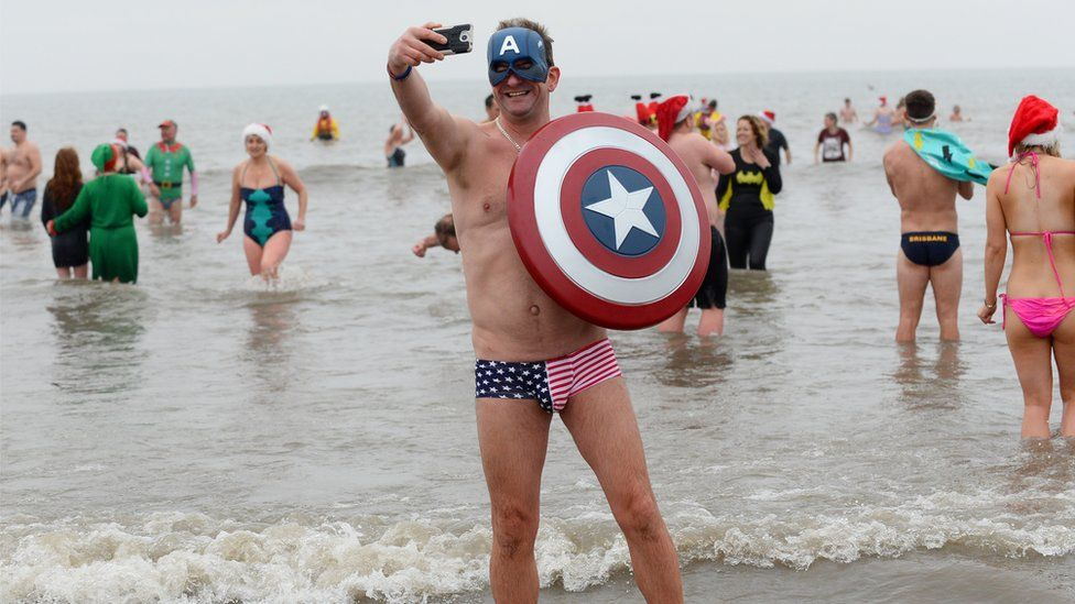 People in fancy dress running into the sea