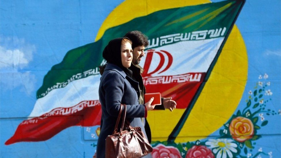 Man and woman walk past a mural of the Iranian flag in Tehran (file photo)