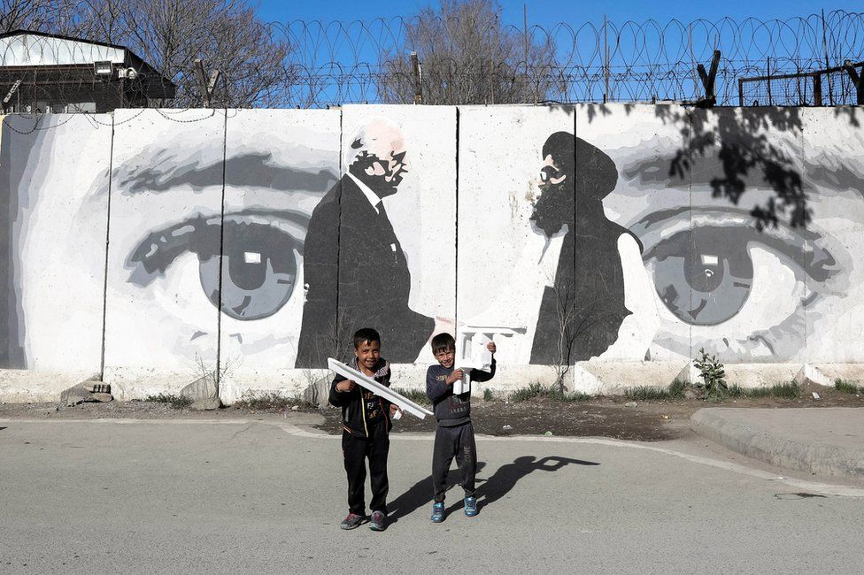 Afghan boys play in front of a wall painted with a photo of Zalmay Khalilzad, U.S. special envoy in Afghanistan (L), and Mullah Abdul Ghani Baradar, the leader of the Taliban delegation
