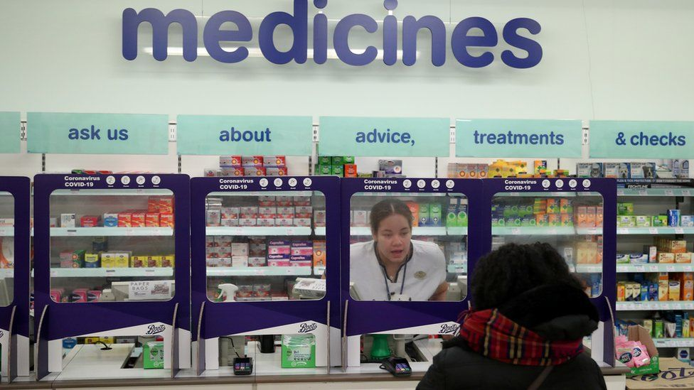 A Boots pharmacist speaking to a customer from behind a safety screen
