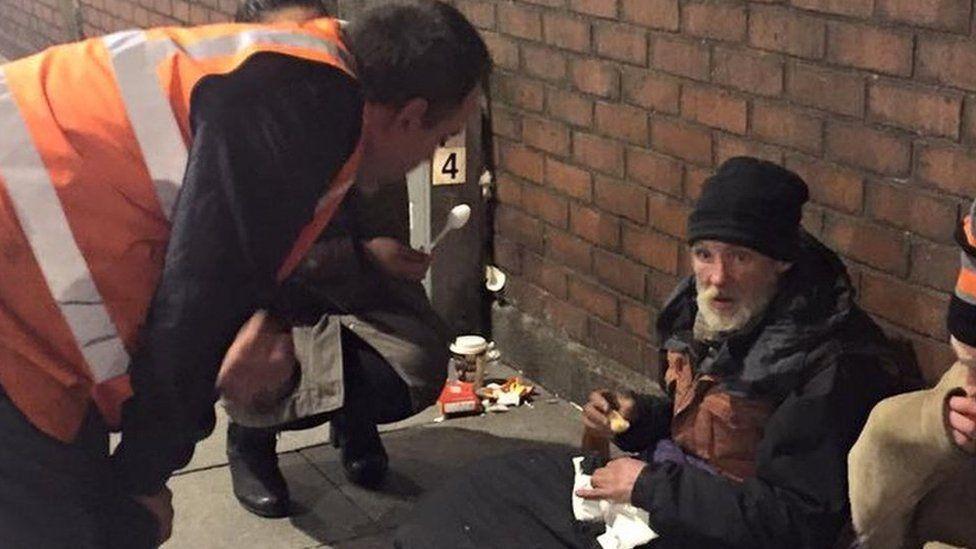 Volunteer helping homeless man