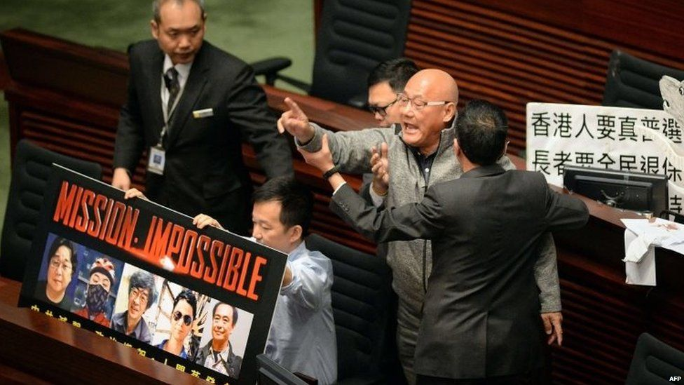Politician Albert Chan is removed from Hong Kong's Legislative Council Chambers for protesting over the missing bookseller during a policy address by the chief executive, Leung Chun-ying