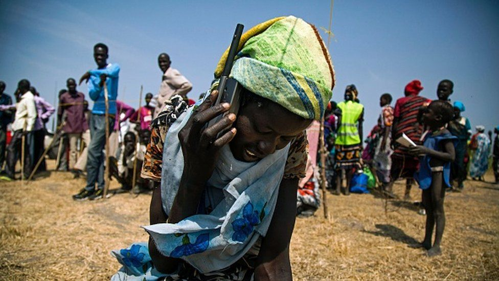 A South Sudanese woman uses a satellite phone provided by International Committee of the Red Cross on 3 February 2016 to call her lost relatives, who fled the village in October 2015