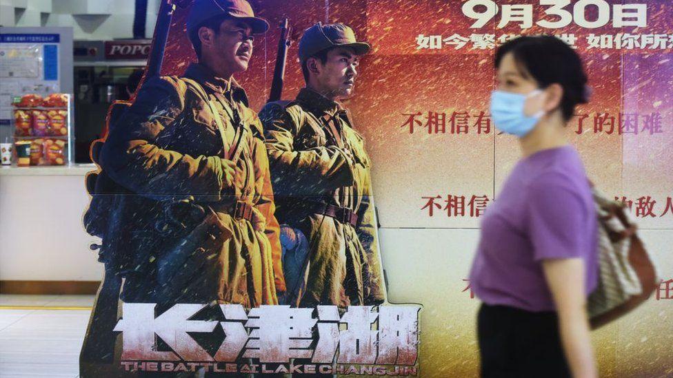 Кинозритель проходит мимо плаката к блокбастеру «Битва на озере Чанцзинь» в кинотеатре Ханчжоу