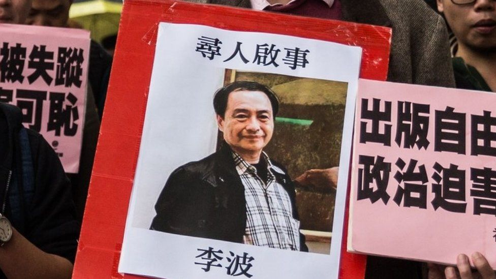 In this picture taken on January 3, 2016, a protestor holds up a missing person notice for Lee Bo, 65, the latest of five Hong Kong booksellers from the same Mighty Current publishing house to go missing, as they walk towards China's Liaison Office in Hong Kong.