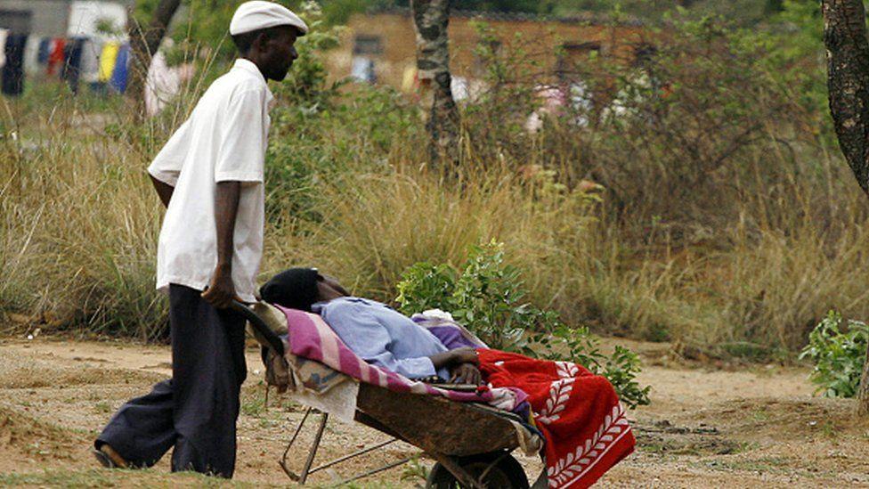 A man pushes his relative in a wheelbarrow to a cholera clinic in Harare, Zimbabwe (05 November 2008)