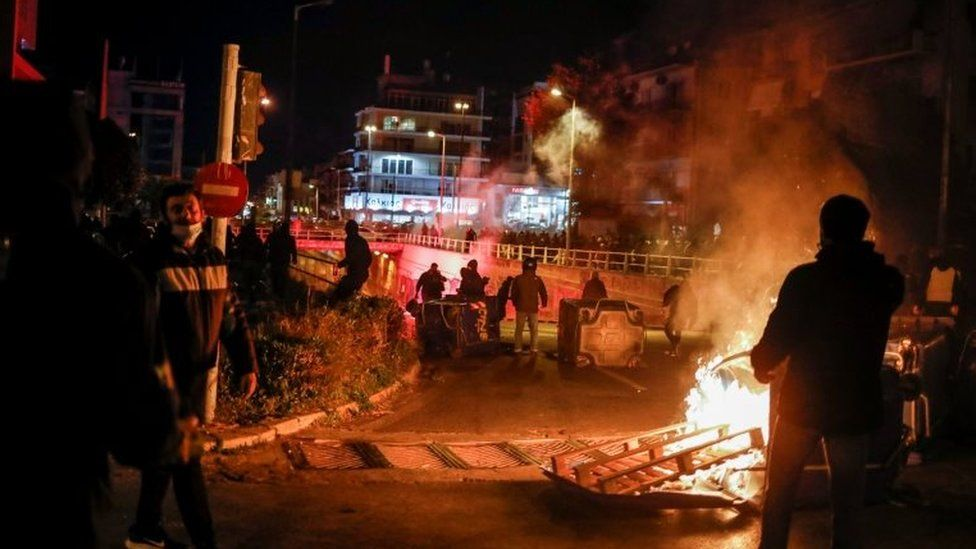 A fire is seen, as protesters clash with police officers during a demonstration