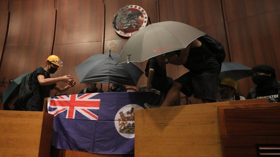 Protesters fix a British colonial flag to the parliament podium after they broke into the government headquarters in Hong Kong on July 1, 2019,