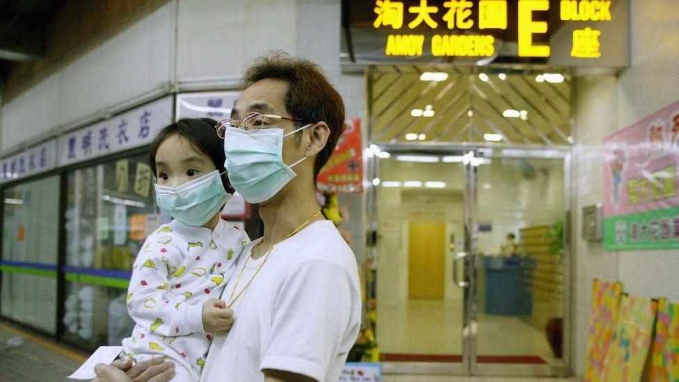 Hombre y niño con mascarilla.