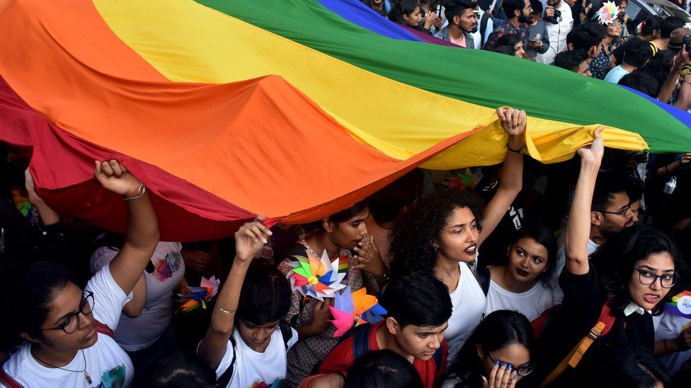 People holding an LGBT rainbow flag at Mumbai's first ever pride march