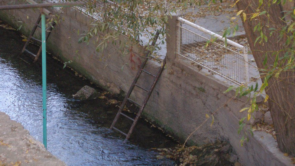 Swimming platform and ladder used by picnicing families in summer along Barada river