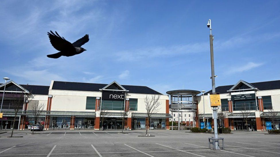 A jackdaw flies over the carpark of a deserted retail park in Llandudno, north Wales