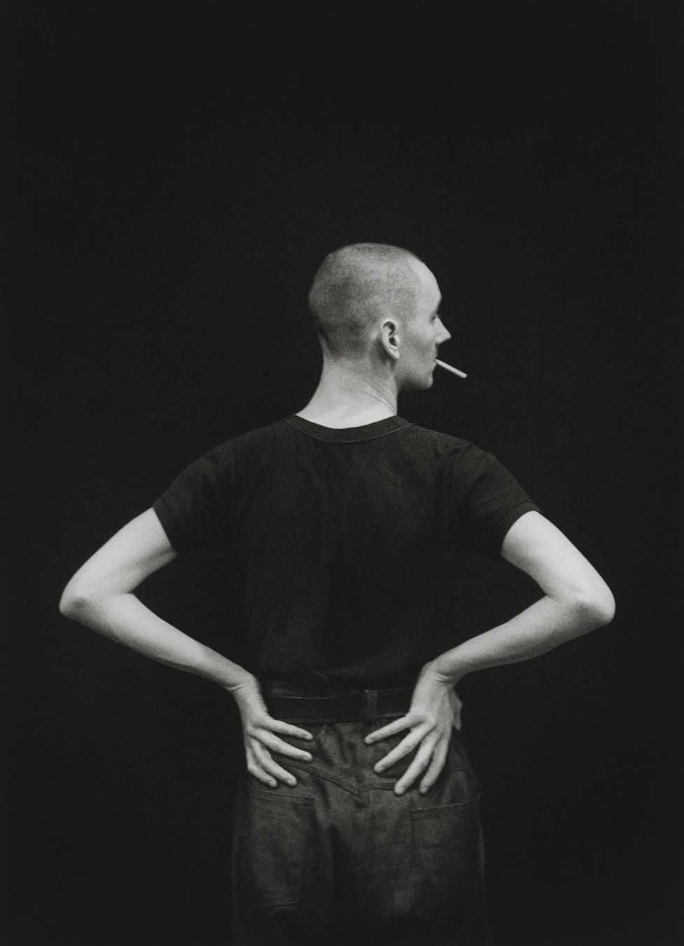 Cerith Wyn Evans stands with a cigarette in his mouth, circa 1984