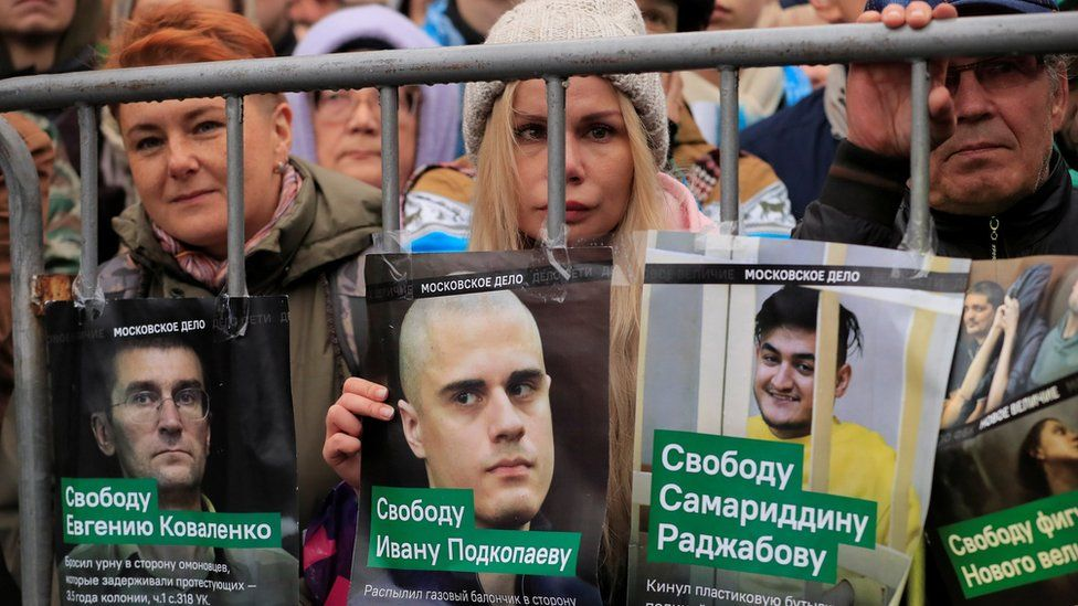 Demonstrators in Moscow hold up posters showing the faces of jailed protesters they demand be freed on Sunday 29 September