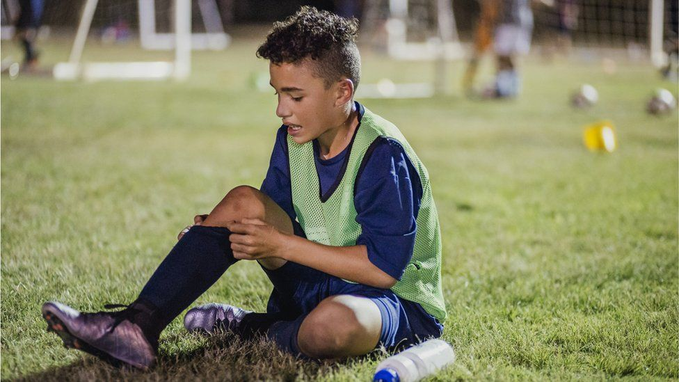 A young football player sitting on the ground looking at his leg
