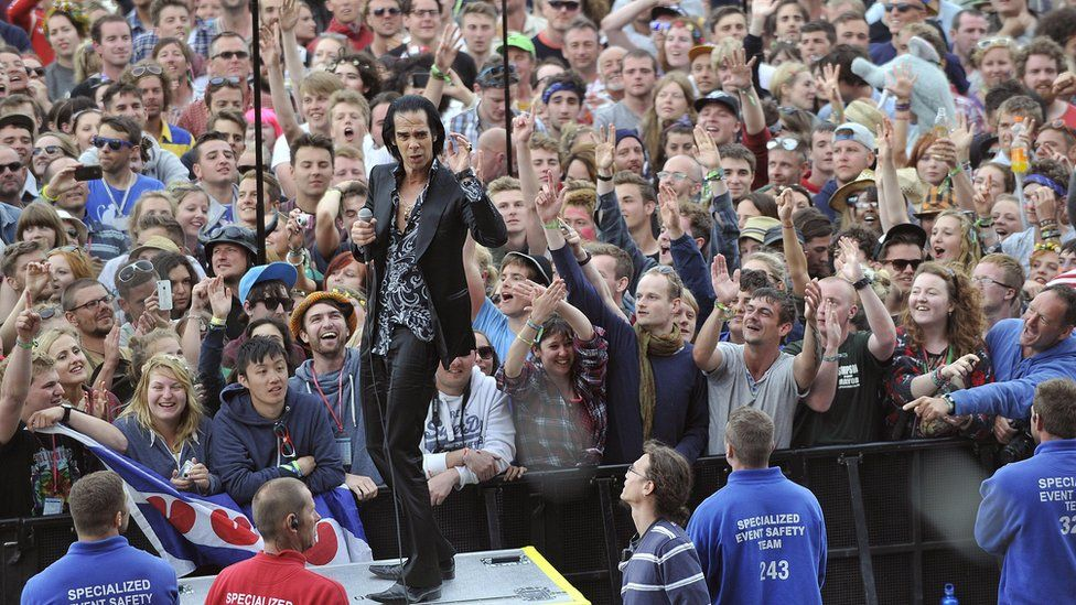 Nick Cave performing for fans at Glastonbury Festival in 2013