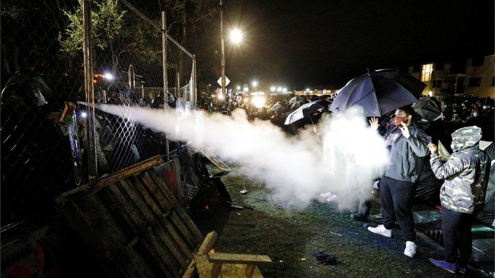 Pepper spray is used from behind the fenced up perimeters of the Brooklyn Center Police Department. 14 April 2021
