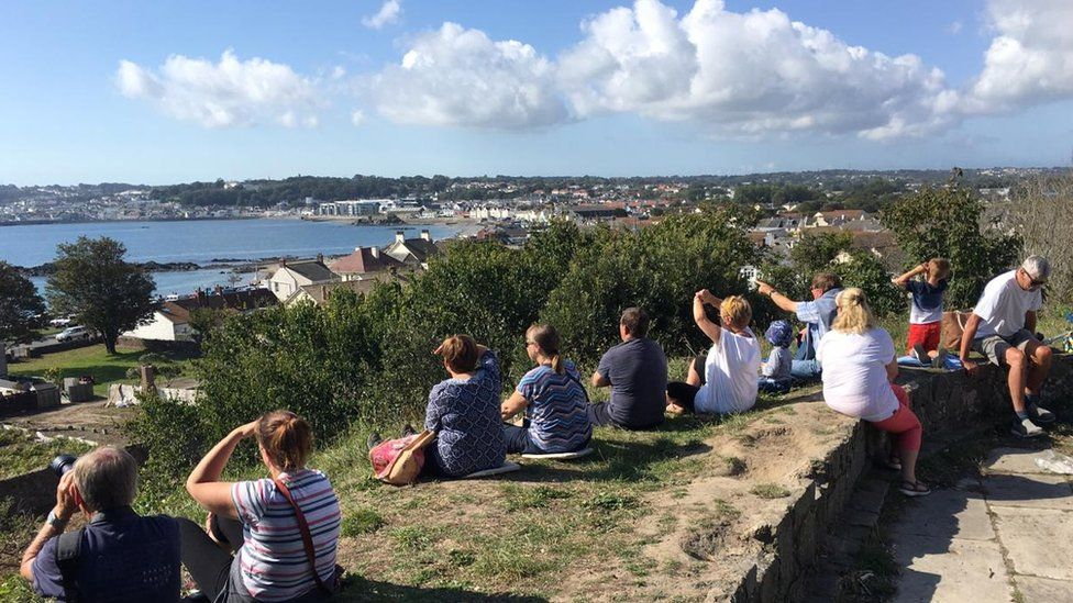 People sat overlooking Guernsey bay