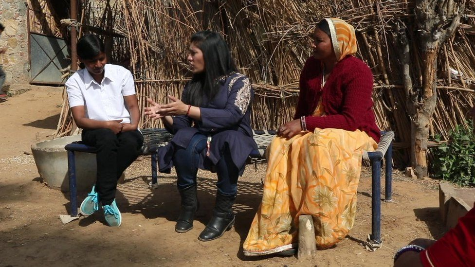 Ajaita Shah (C) trying to persuade a villager that solar alternatives are a more reliable solution to the lack of regular electricity.
