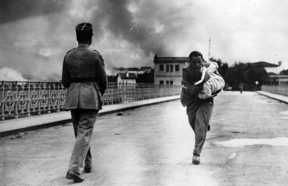 Journalist Raymond Walker risks his life under a hail of bullets dashing across the international bridge from Hendaye, France, to Irun, Spain to save a baby, during the Spanish Civil War