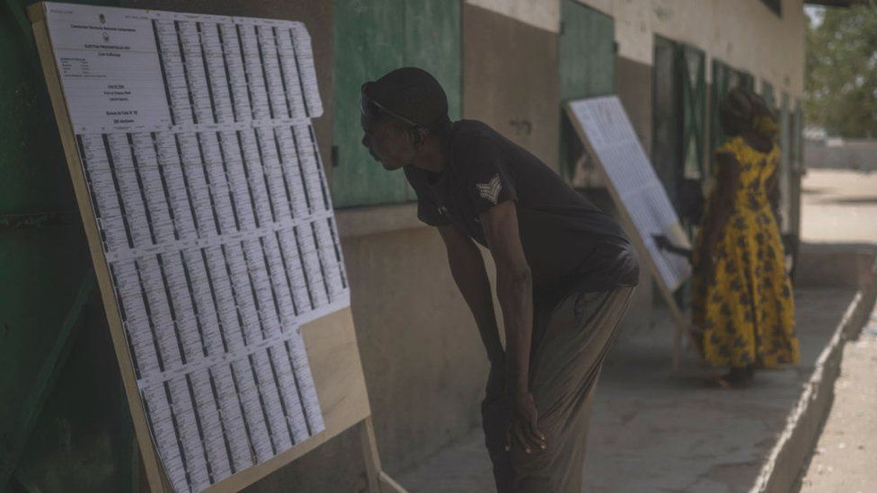 A man searches for his name on the voter's roll at a polling station in N'Djamena on April 11, 2021