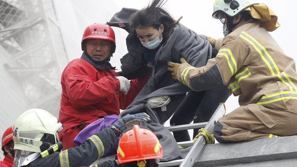 Rescuers help a survivor escape the collapsed building in Tainan, Taiwan, on 6 February 2016