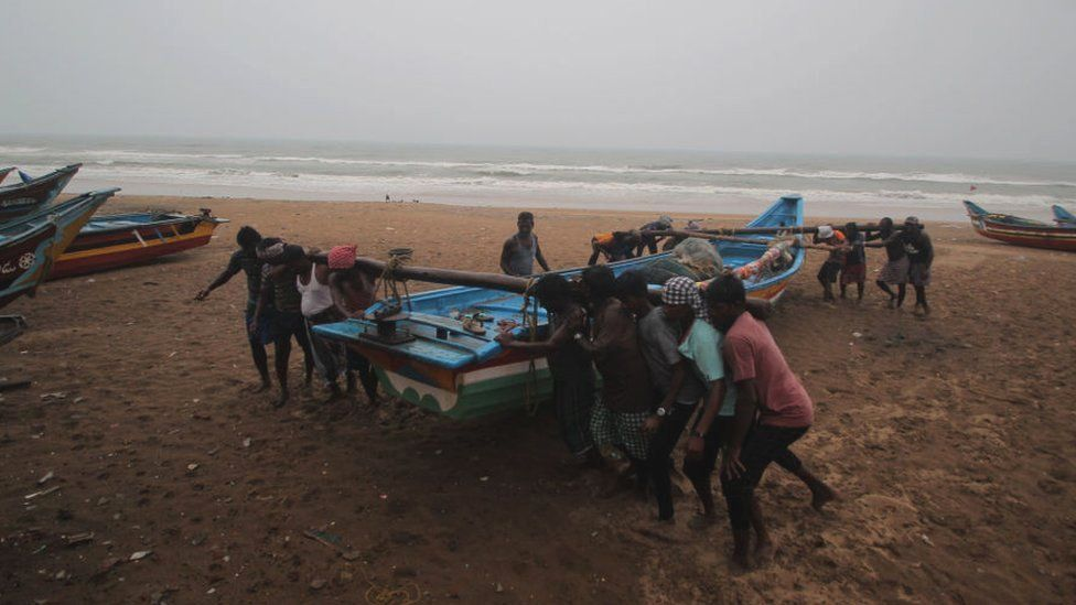 Fishermen move their fishing boats to safety in preparation for Cyclone Yaas
