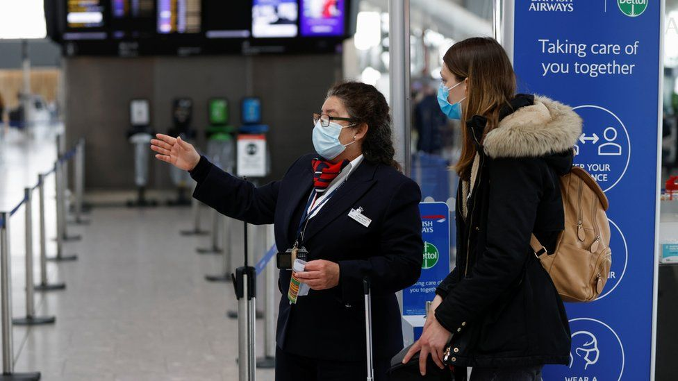Passenger and staff at Heathrow Airport