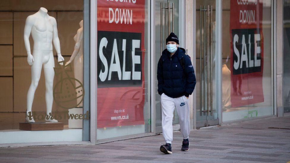 Man walking past closed down shop