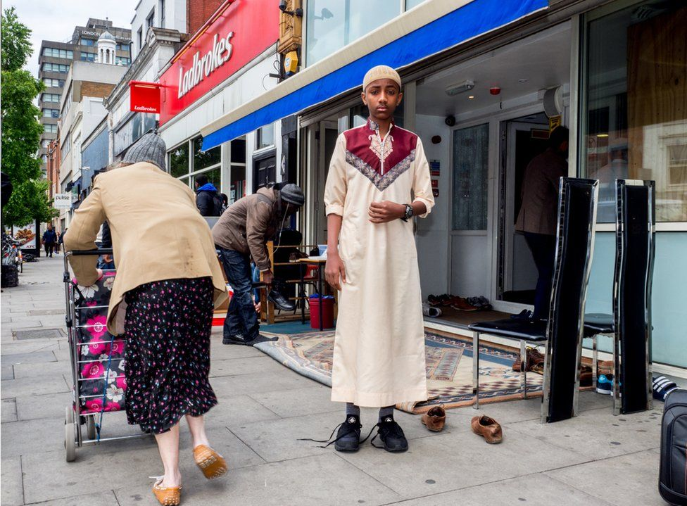 A young worshipper arrives for Friday prayer at the Holloway Mosque in London.