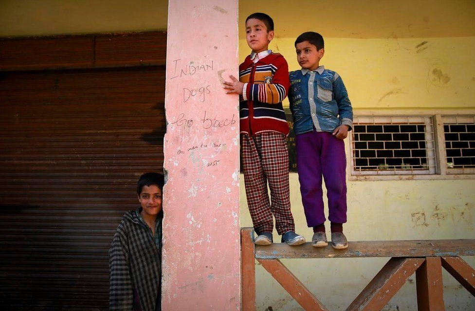Children stand next to anti-India graffiti on the school wall