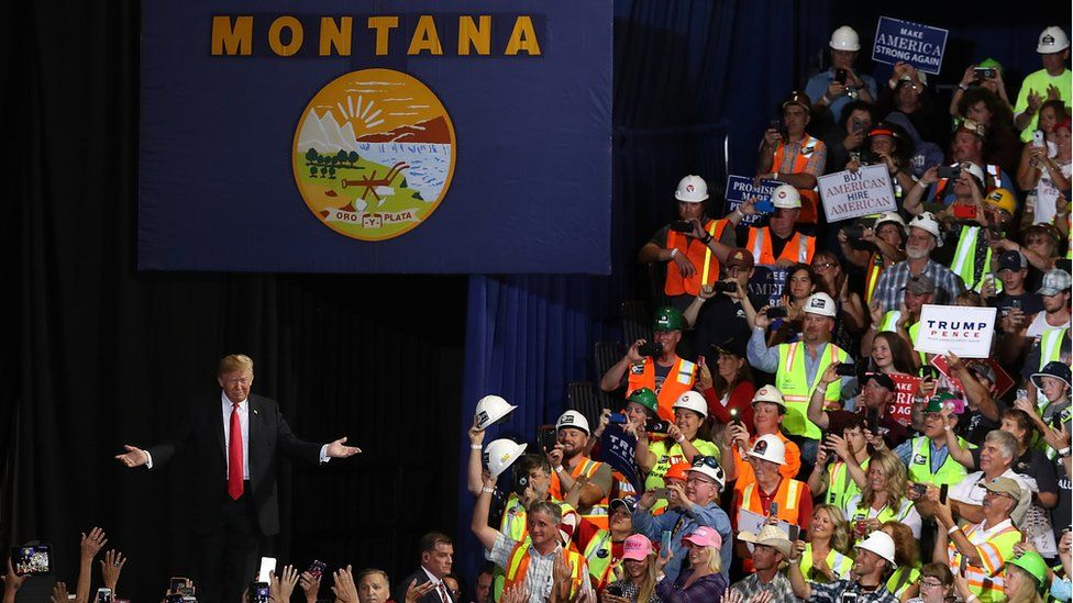 Trump greeting supporters under a banner with Montana written on it
