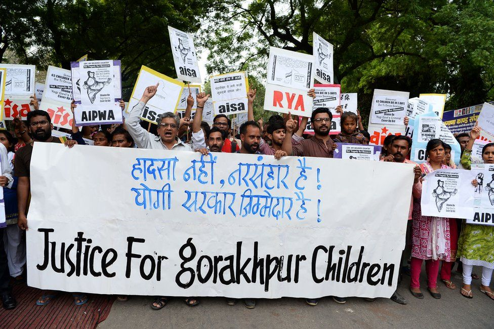 Protestors hold placards and shout slogans against the deaths of at least 64 children at the Baba Raghav Das Hospital in Gorakhpur.