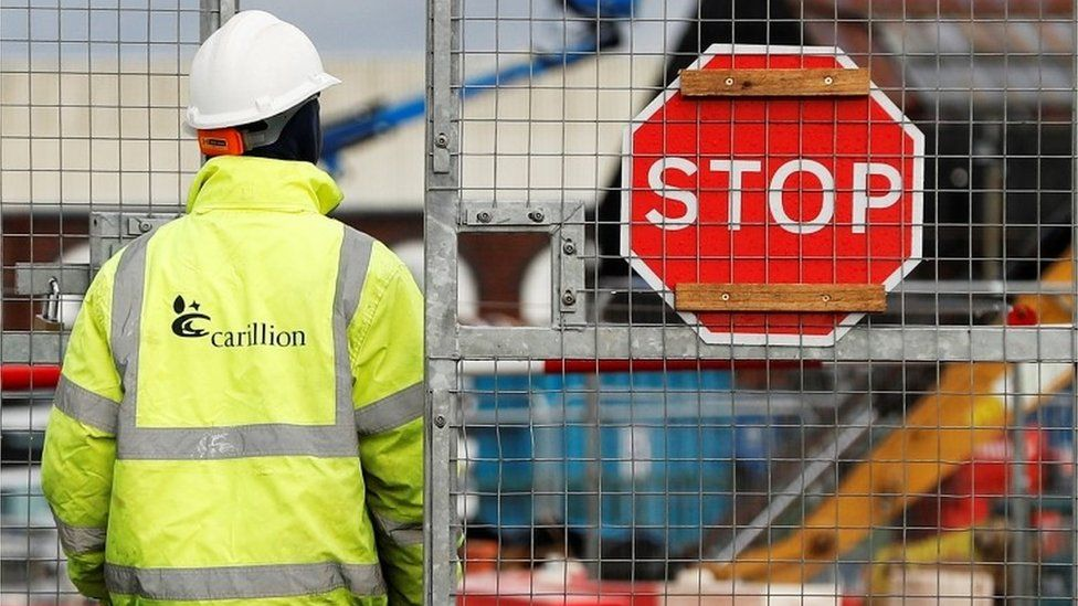 Carillion worker in front of metal fence