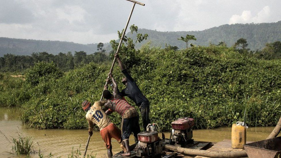 A group of Galamseyer, illegal gold panners, uses a motorised pump to scrap the river bed as they look for speck of gold, in Kibi area, southern Ghana on April 12, 2017.