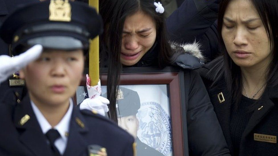 Wenjian Liu's widow, Pei Xia Chen, weeps while clutching a photo of the dead policeman at his funeral in New York, 4 January